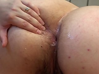 A fat woman stuffs cucumbers into her ass.